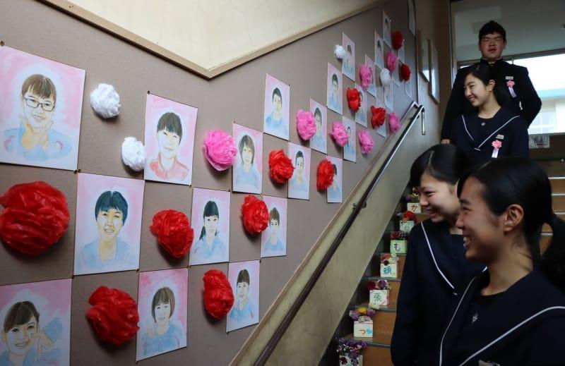 階段に飾られた似顔絵に笑顔を見せる卒業生=雲仙市、小浜中