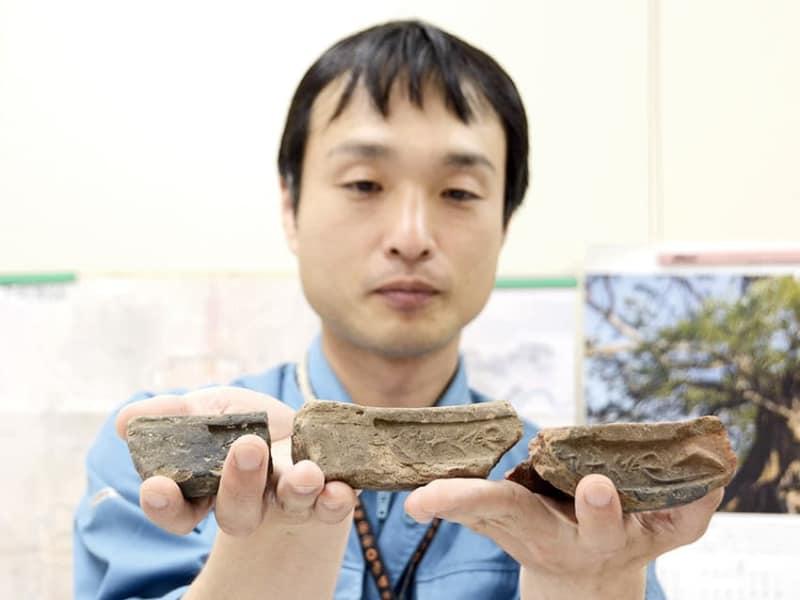 天正時代の銘が入った瓦を持つ関根章義さん。大天守の石垣から出土した=熊本城調査研究センター