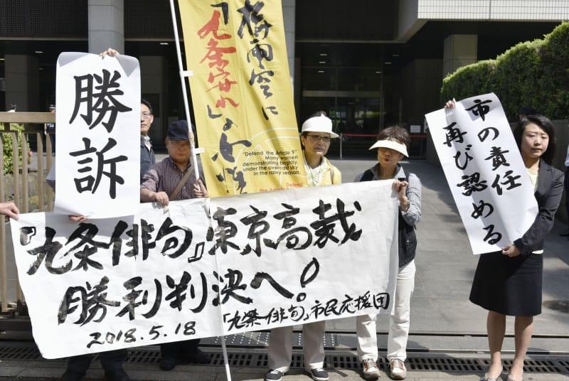東京高裁の判決後、「勝訴」の文字を掲げる原告側の支援者ら=18日午後、東京都千代田区