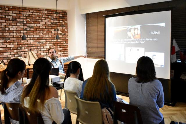「虹色カフェ」の参加者を前にLGBTなどについて説明するエリック・ボンド准教授=7日午後、宮崎市・宮崎国際大の国際交流ラウンジ