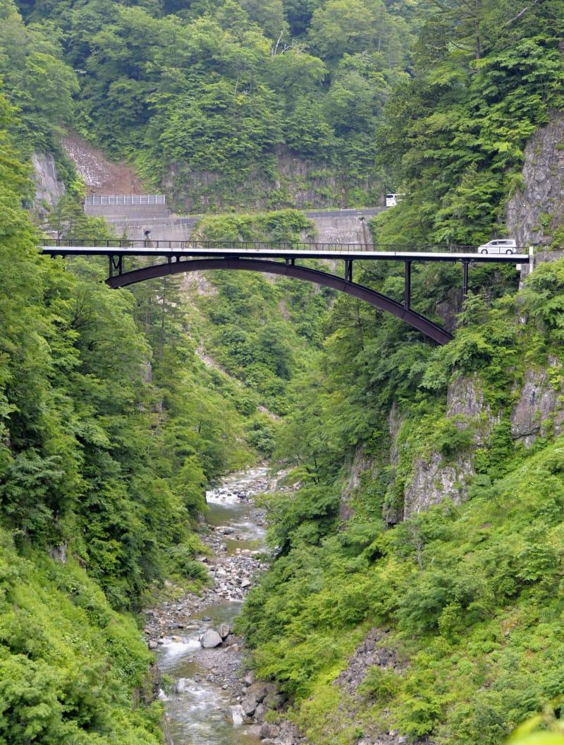 「白山白川郷ホワイトロード」が全線開通し、新緑の渓谷にかかる橋を走る車=15日午前、石川県白山市