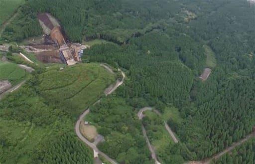 県の砂防工事現場(左奥)下側の長寿ケ丘公園脇を通る阿蘇市道狩尾幹線。右下側の麓側からの約2キロ区間が本年度内に開通する見込み=阿蘇市(同市提供)