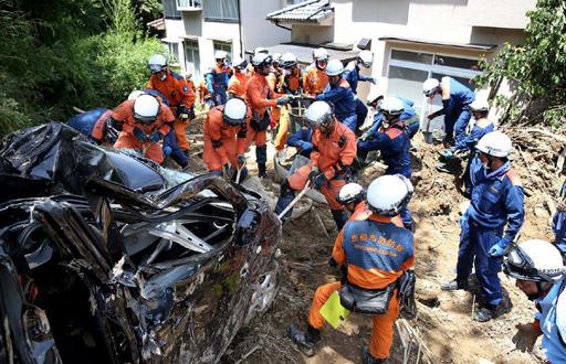 土砂で押しつぶされた車の周囲で行方不明者の捜索を続ける消防隊員(13日午前11時40分、広島県熊野町川角5丁目)