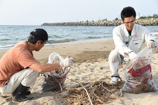 砂浜に漂着したごみを拾う参加者=13日、鳥取市の賀露西浜海岸
