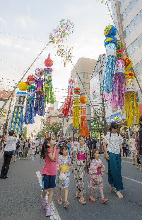 七夕飾りで彩られた通りを歩き、祭りを楽しむ子どもら=13日午後6時半ごろ、八戸市三日町