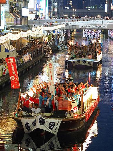 夜の川面をにぎやかに航行する渡御船団=13日、大阪市中央区の道頓堀川