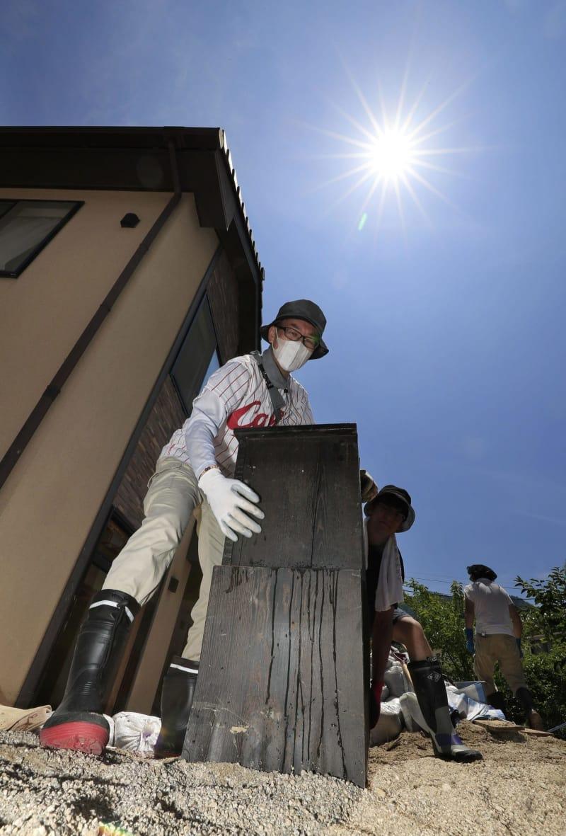 強い日差しの中、被災した住宅から家財道具を運び出すボランティア=14日午前11時1分、広島県坂町