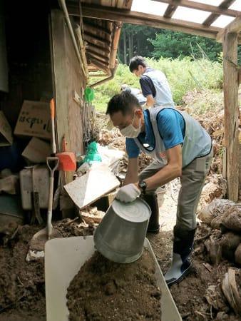 土砂崩れで民家裏に堆積した土砂を取り除くボランティアたち(14日午前11時16分、福知山市上大内)