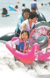 海開きした菖蒲田海水浴場で水遊びを楽しむ家族連れ=14日午前11時10分ごろ、宮城県七ケ浜町の菖蒲田浜