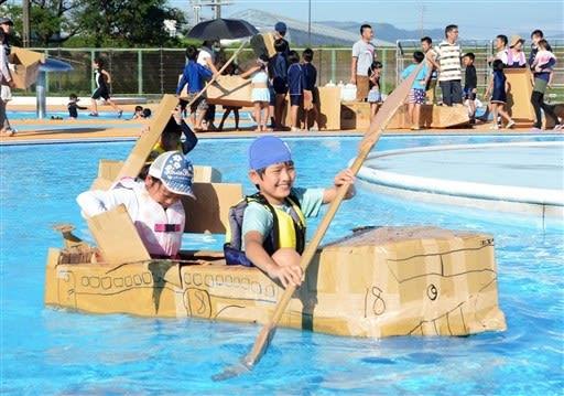 段ボールで作ったボートでゴールを目指す子どもたち=益城町