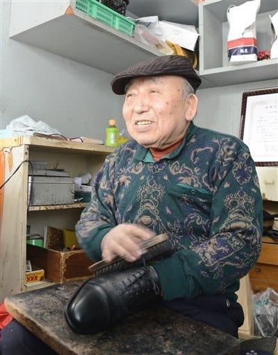靴を磨きながら常連客との会話を楽しむ鈴木田袈裟雄さん