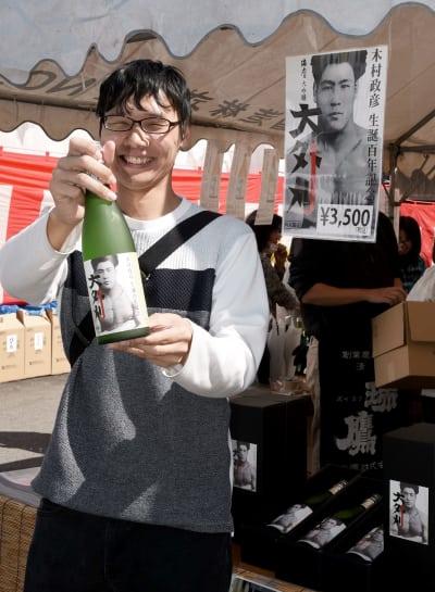 木村政彦氏にちなんだ大吟醸酒「大外刈」を手に笑顔を見せる購入客