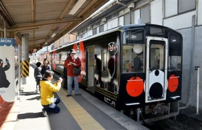 八代駅に到着したくまモンラッピング列車3号を写真に収めるくまモンファンら