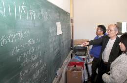 メッセージが書かれた黒板を確かめる柳沼准教授(右から2人目)ら=2月8日、福島県川内村