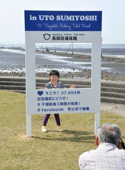 SNS映えを意識して設置された長部田海床路の看板で写真を撮る家族連れ