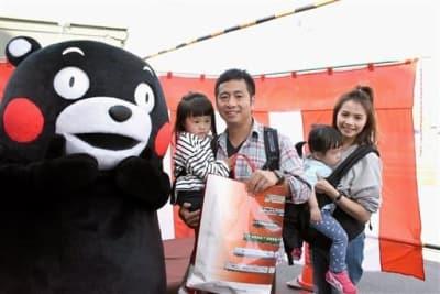 くまモンラッピング電車を利用した外国人観光客として10万人目となった梁思偉さん(中央)と家族