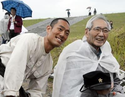 撮影の合間に懇談した中村勘九郎さん(左)と「走れ二十五万キロ」の著者長谷川孝道さん