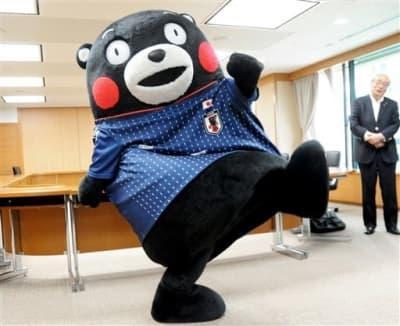 サッカー日本代表ユニホームを着てシュートポーズをとるくまモン
