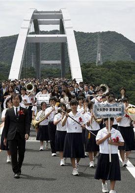 大矢野中吹奏楽団を先頭に、新天草1号橋(天城橋)の渡り初めをする関係者たち