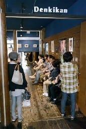 映画の上映時間が近づき、入場を待つ観客たち=熊本市中央区のDenkikan