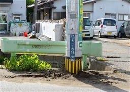 液状化で地中に沈み込んだ電柱。周囲には砂と水が噴き上げた跡がある=熊本市南区