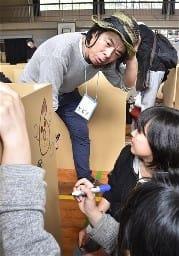 段ボール製ベッドに絵を描く子どもたちと日比野克彦さん(奥)=熊本市中央区の城東小
