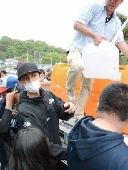 水を届けた俳優の高良健吾さん。高良さんから水をもらおうと行列ができた=熊本市西区