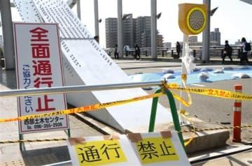 地震で損傷し、通行が禁止されている白川橋だが、徒歩で渡る人が後を絶たない=熊本市西区