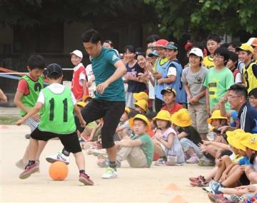 子どもたちとのミニゲームで、華麗なドリブルを披露するドルトムントの香川真司選手=24日午後、熊本市東区の若葉小(谷川剛)