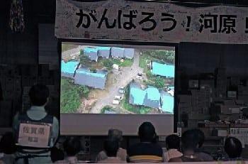 小型無人機で撮影された被災状況の映像が上映された西原村の河原小体育館=7日夜