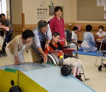 力を合わせてストライクを狙う愛泉会日南病院入所者と家族