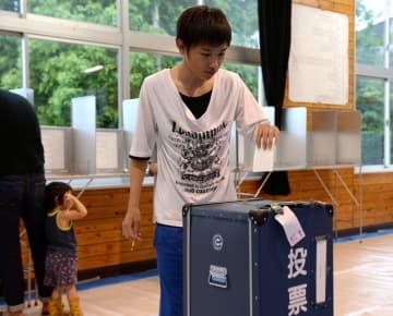投票する高校生。18歳選挙権で有権者となった若者など、県民はそれぞれの思いを1票に込めた=10日午前、宮崎市・恒久小