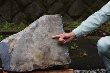崩れた石垣の表面に彫られているのが見つかった人形の線画=12日午後、熊本市中央区(大倉尚隆)