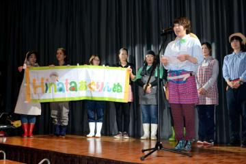 作業着姿でお披露目会のステージに上がり、活動への意気込みを語る「Hinata・あぐりんぬ」のメンバーたち=13日午後、宮崎市
