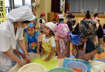 料理教室でニンジンなど野菜を切る作業を体験する園児たち