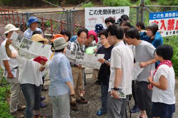 佐藤さん(中央)から鉱山の説明を受ける水俣市の市民ら