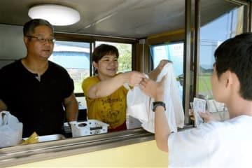 再開した店で、揚げたての唐揚げを客に渡す宮崎さん夫婦=阿蘇市