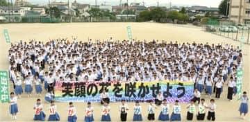 蒲町中から贈られた横断幕を持つ出水中の全校生徒=熊本市中央区