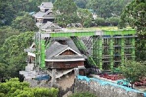 倒壊防止工事のため、緑色の鉄骨で覆われた熊本城の飯田丸五階櫓。鉄骨の「腕」の先端に、灰色の支柱がセットされており、今後の工事で櫓の下に差し込まれる=25日午前、熊本市中央区(高見伸)