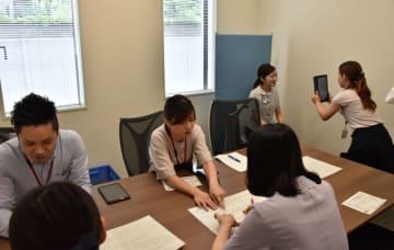 宮崎銀行都城営業部に出向き、タブレット端末を使って行員のマイナンバーカード申請を手伝う市職員ら