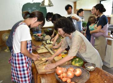 郷田美紀子さん(右手前)から指導を受けながら調理する参加者たち