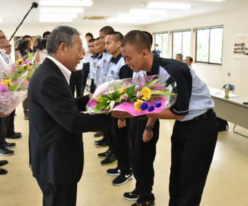 JA宮崎中央の藤原組合長(左)から歓迎の花束を受け取るインドネシアからの実習生たち