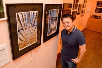 写真展で宮崎市田野町の大根やぐらの様子を展示している山本さん=東京都中央区