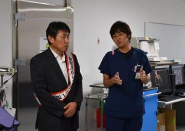 都城夜間急病センターの一日所長に招かれ、医師から施設の説明を受ける三股町の西村副町長(左)