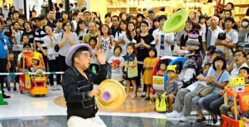 大勢の買い物客らが華麗な技に見入った、ブライアン・ドレスナーさん(中央)のジャグリング=2日午後、宮崎市・イオンモール宮崎