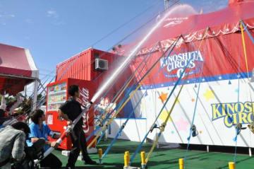 動力消防ポンプで赤テントを目掛けて放水する団員ら=11日午前、宮崎市・イオンモール宮崎特設会場