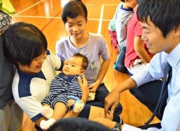 9月20日に誕生した肥後教諭(右)の長男高正ちゃんをいとおしそうに抱っこし、「うわあ、あったかい」などと感嘆の声を漏らす児童=11月13日、都城市・今町小