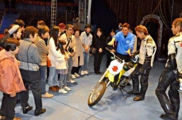 ショーで使用するオートバイの説明を受ける参加者=26日午後、宮崎市・イオンモール宮崎特設会場