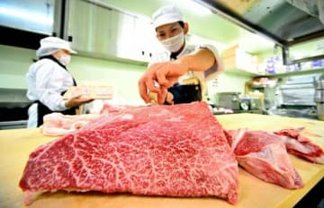 「いい肉の日」に向けて、すき焼きやしゃぶしゃぶ用の宮崎牛もも肉を切り、形を整える従業員=28日午後、宮崎市源藤町のAコープオランヴェル