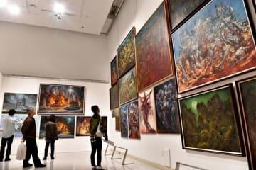 故生賴さんの絶筆となった未完作や晩年の作品などに見入る来場者たち=3日、宮崎市・みやざきアートセンター